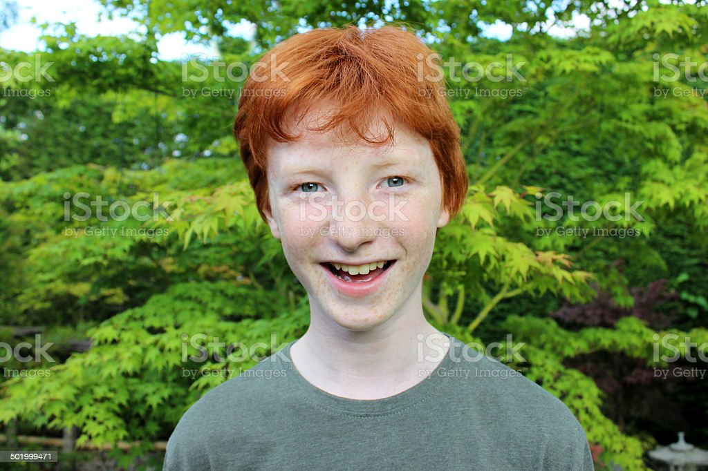 Happy boy in garden, short red hair image, smiling, laughing stock photo