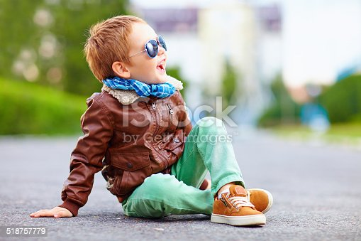 istock happy boy in leather jacket posing on the ground 518757779