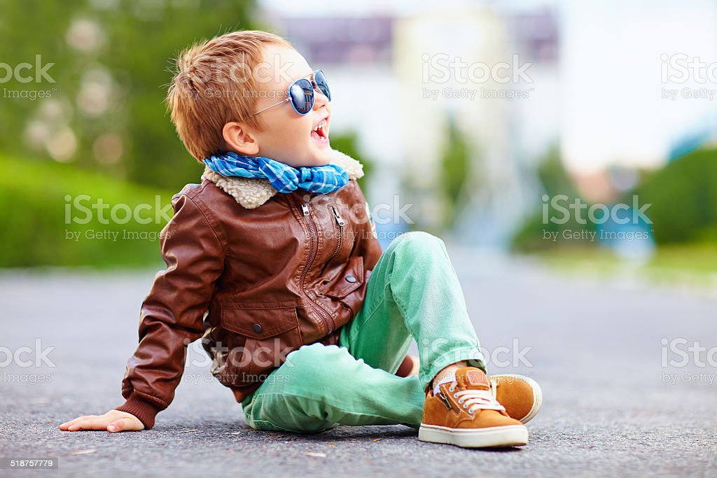 happy boy in leather jacket posing on the ground stock photo