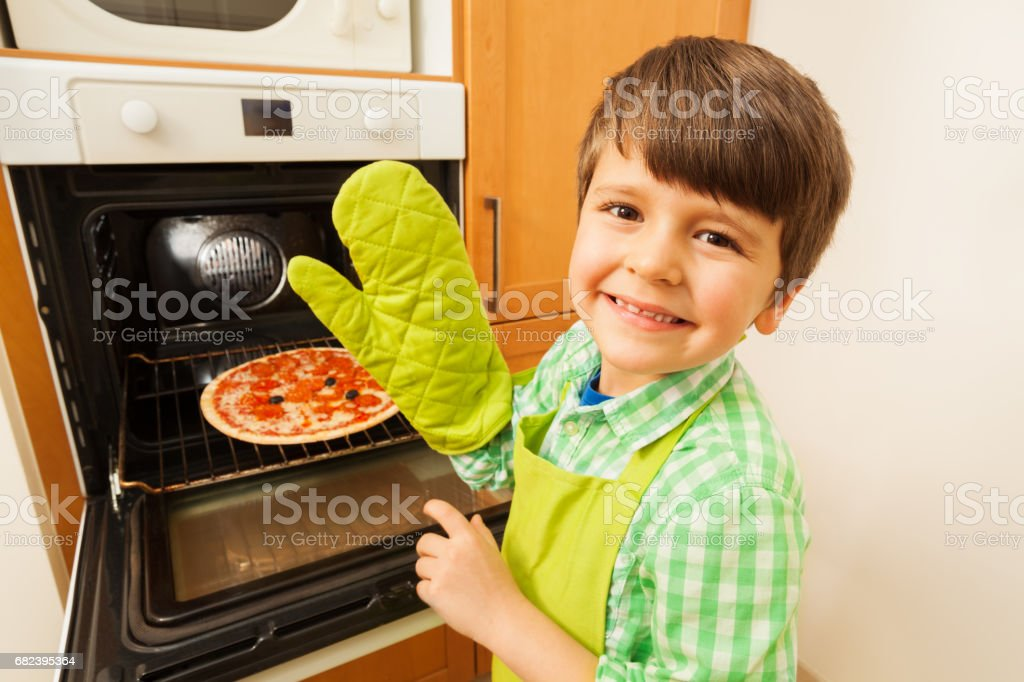 Happy boy in mitten getting hot pizza out of oven royalty-free stock photo