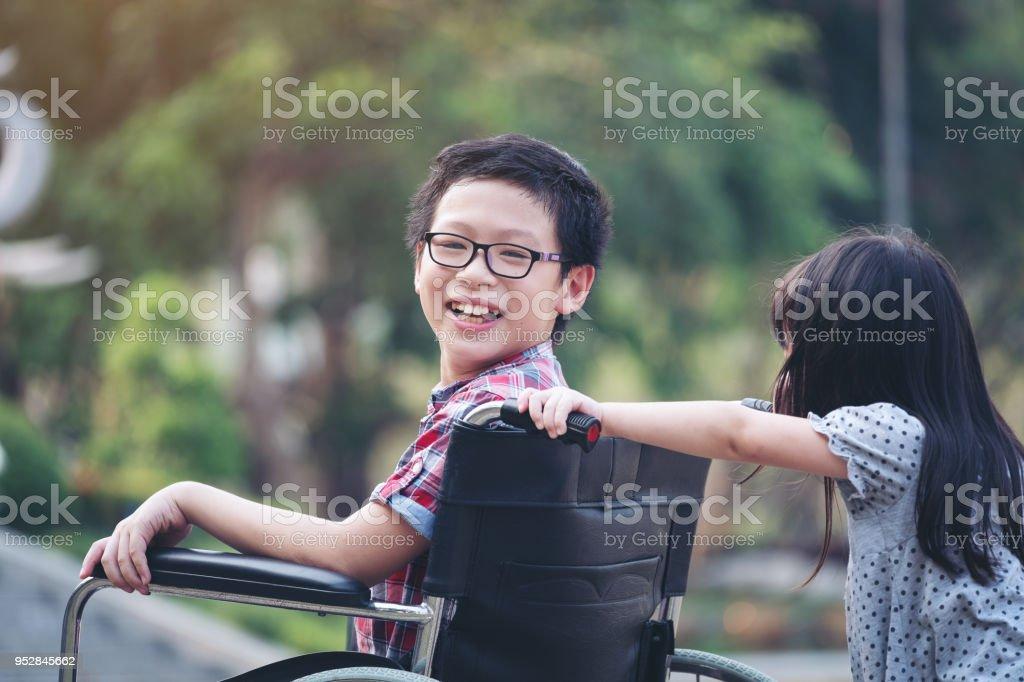 Fröhlicher Junge im Rollstuhl mit Mädchen versuchen Antrieb Rollstuhl von ihrem Bruder Lächeln, Zeit mit der Familie – Foto