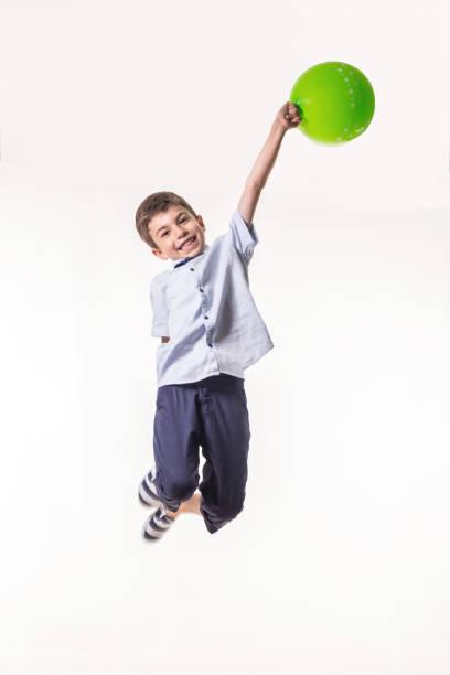 fröhlicher junge jummping wit ballon auf weißem hintergrund - ballonhose stock-fotos und bilder