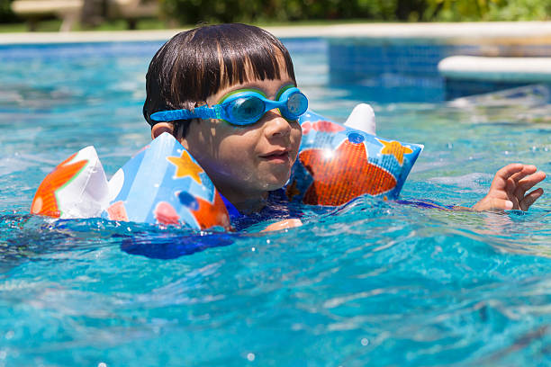 Happy Boy learning to swim stock photo