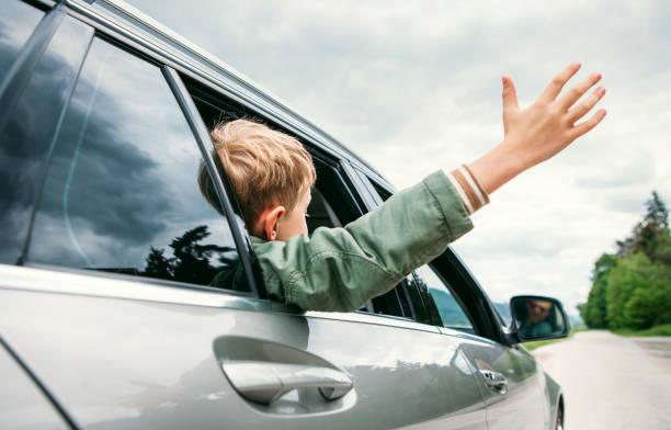 heureux garçon vue depuis la fenêtre de l'auto - homme faire coucou voiture photos et images de collection