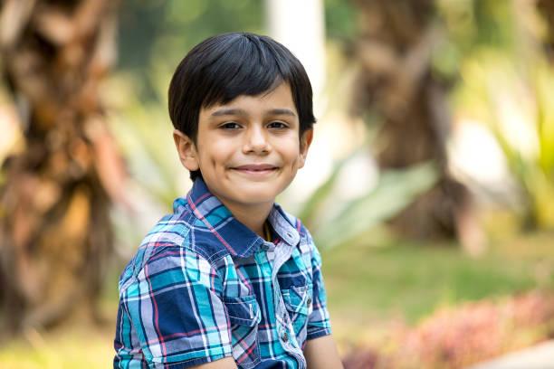 Happy boy looking at camera at park stock photo