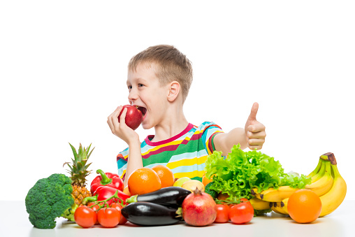 istock Happy boy on a diet with food, eating a red apple sitting at the table 1160108925