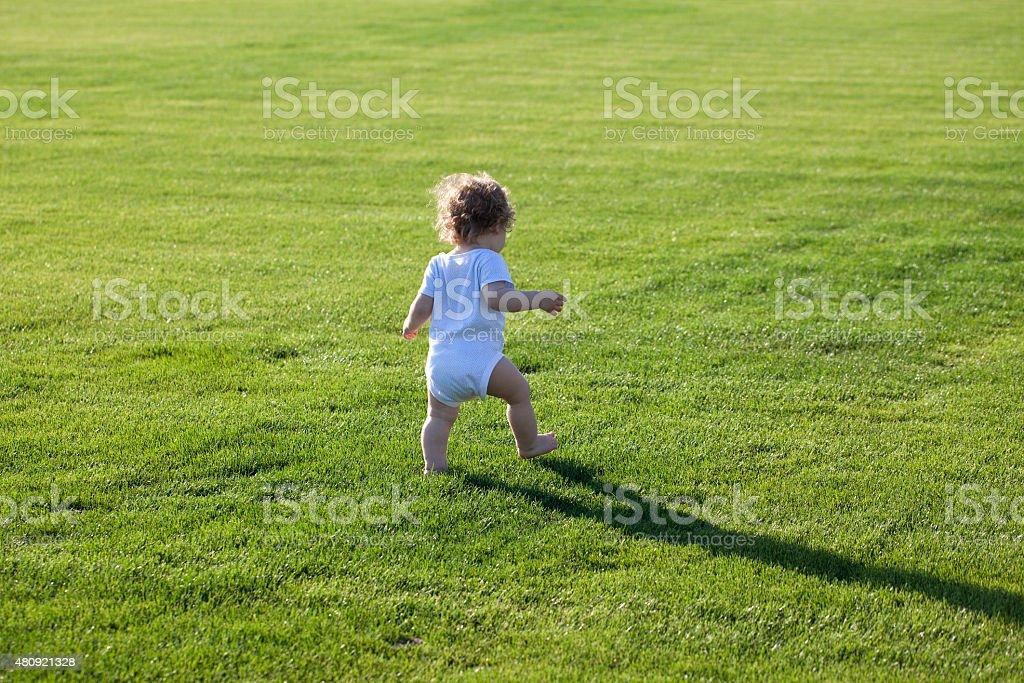 Happy boy on green grass stock photo