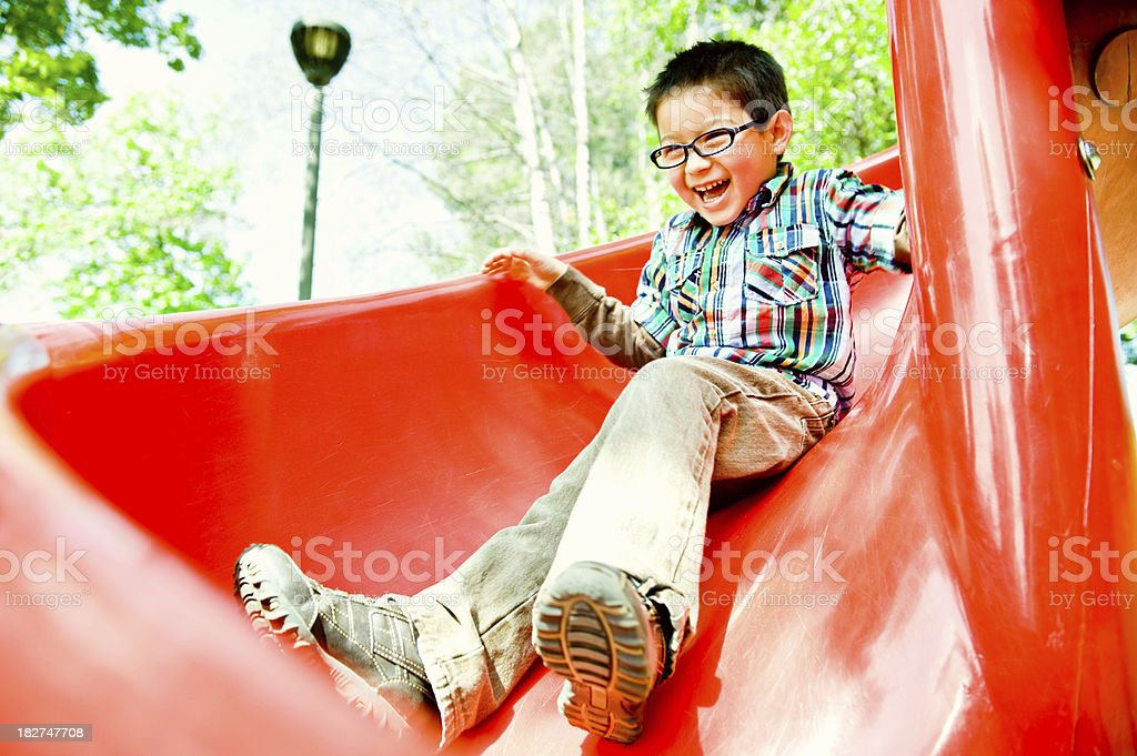 happy boy on red slide stock photo