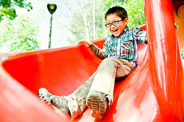 happy boy on red slide stock photo