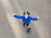 Happy boy on roller skates showing hands up