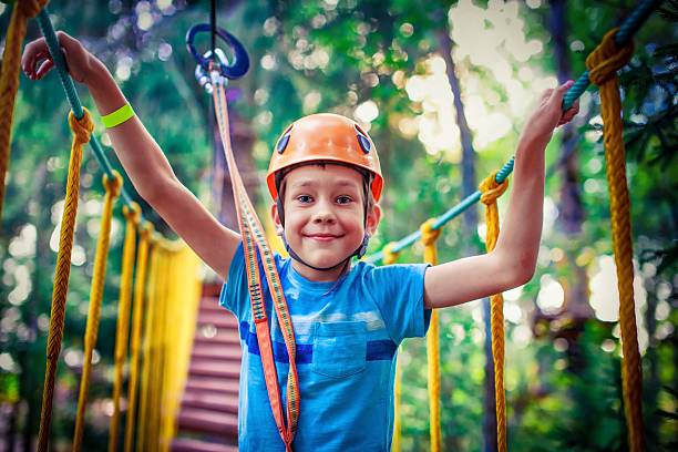 happy boy on the zipline proud of his courage the child in the high wire park. hanging bridge. HDR zip line stock pictures, royalty-free photos & images