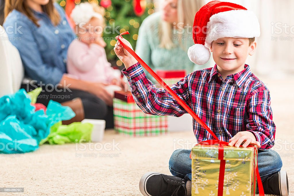 Happy boy opens gift at Christmastime stock photo