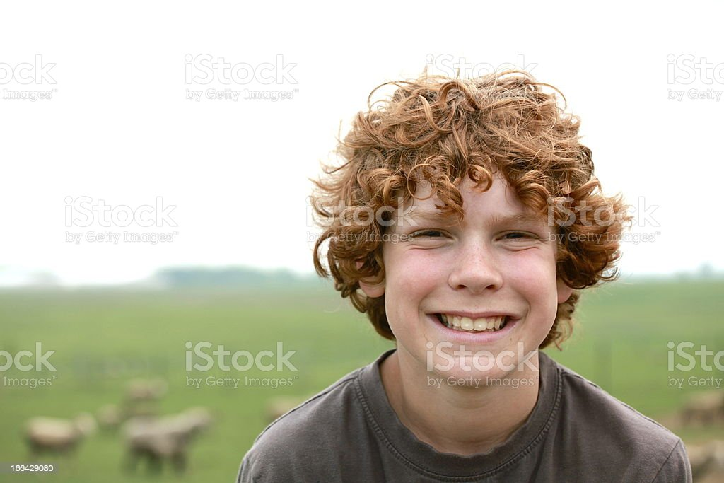 Happy Boy Outside by Field of Sheep stock photo