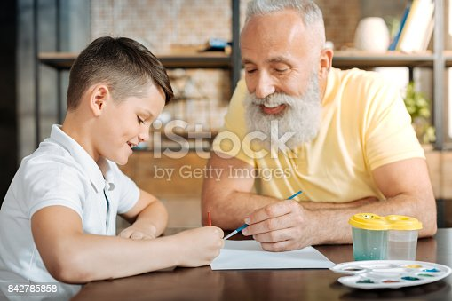 istock Happy boy painting a picture together with his grandfather 842785858
