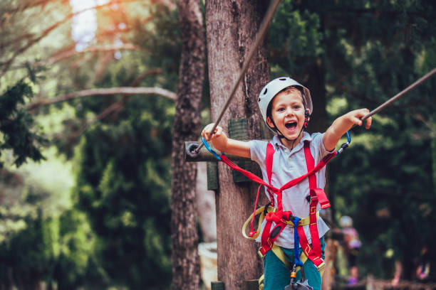 Happy boy playing at adventure park on sunny day. Little boy climbing in adventure activity park with helmet and safety equipment zip line stock pictures, royalty-free photos & images