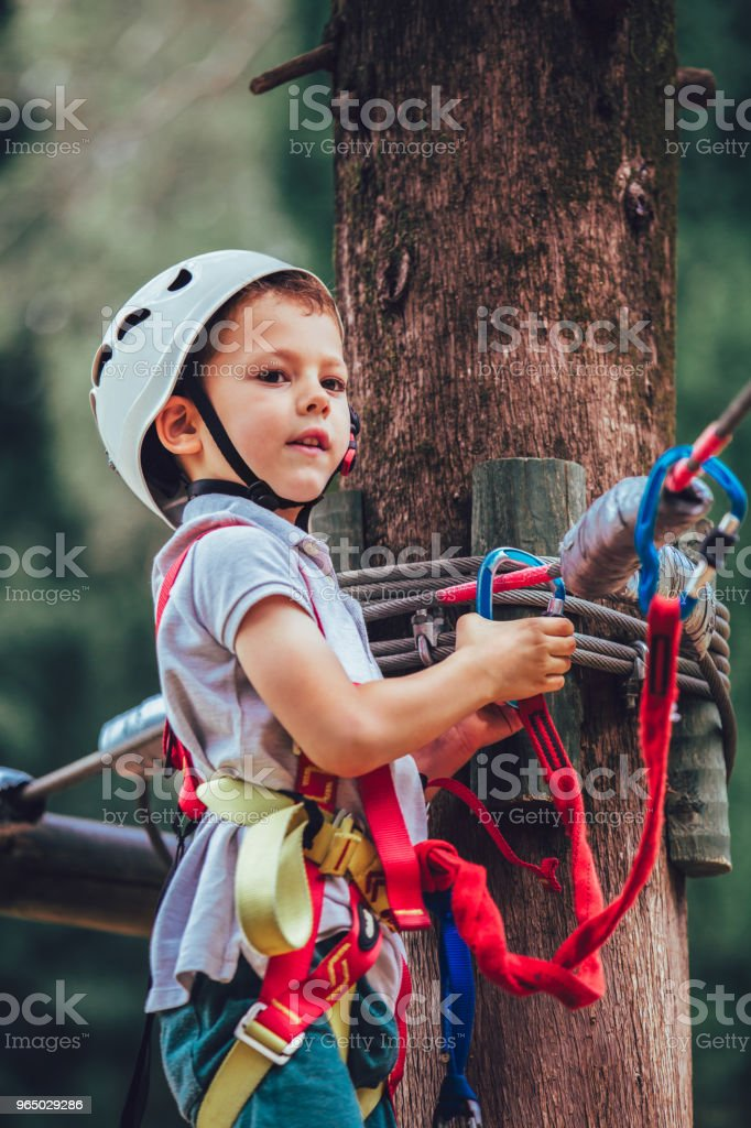 Happy boy playing at adventure park on sunny day. royalty-free stock photo