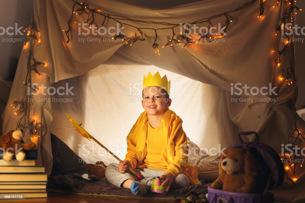 Happy boy playing at home in a tent stock photo