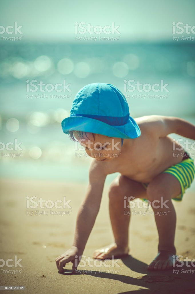 Happy boy playing on the beach stock photo