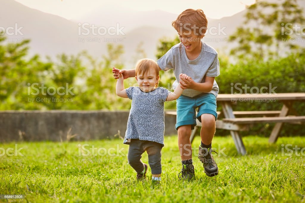 Happy boy playing with toddler on grassy field Happy boy playing with toddler on grassy field. Kids are wearing casuals. They are enjoying at back yard. 10-11 Years Stock Photo