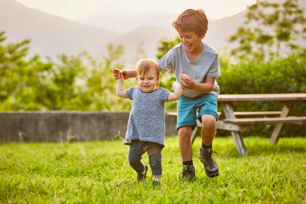 Happy boy playing with toddler on grassy field stock photo