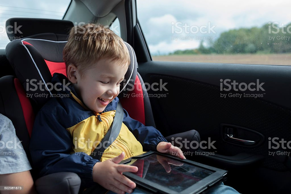 Happy boy playing with touchpad in the car stock photo