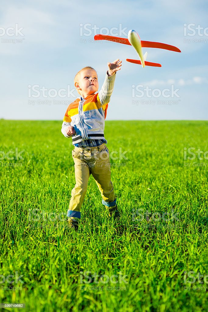 Happy boy playing with toy airplane against blue summer sky stock photo