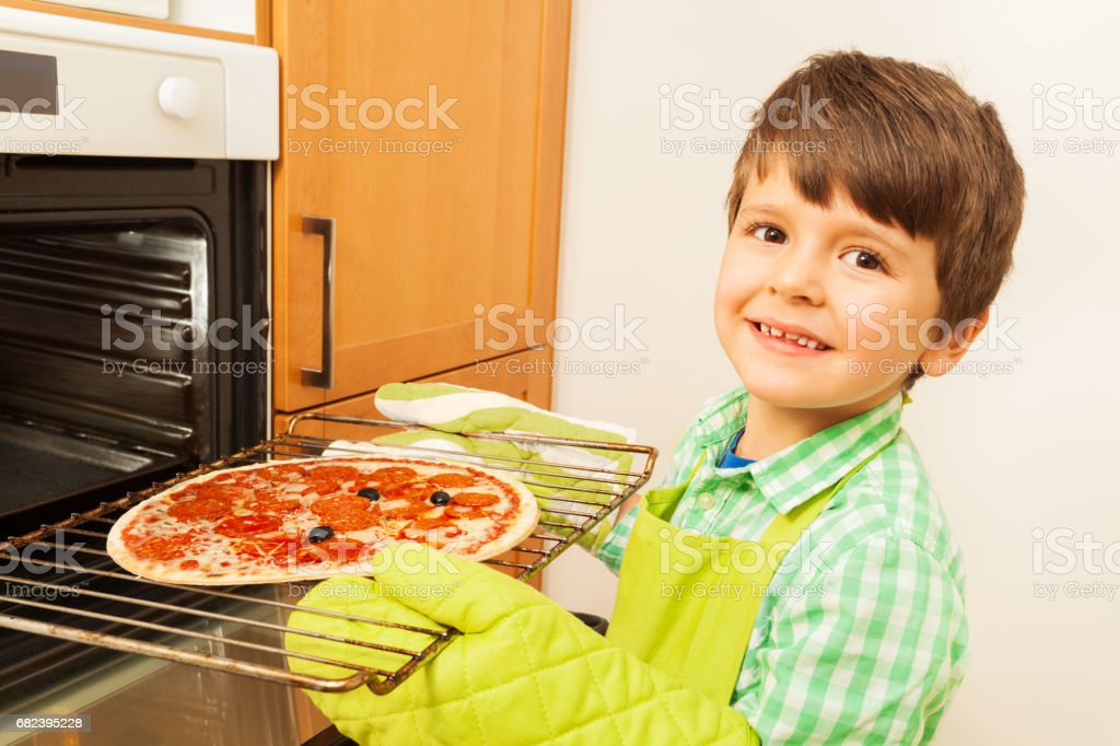 Happy boy putting homemade pizza in the oven foto stock royalty-free