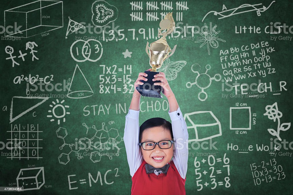Happy boy raising trophy in class stock photo