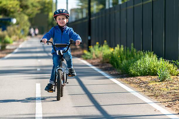 happy boy riding his bicycle on bike lane - fahrradwege stock-fotos und bilder