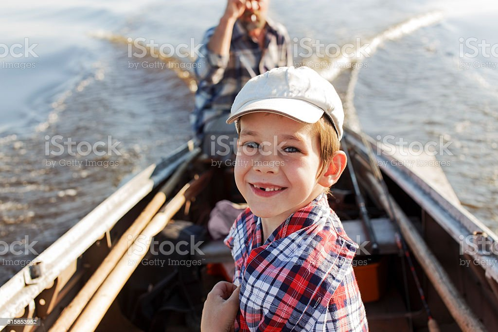 happy boy riding in a boat with his grandfather stock photo