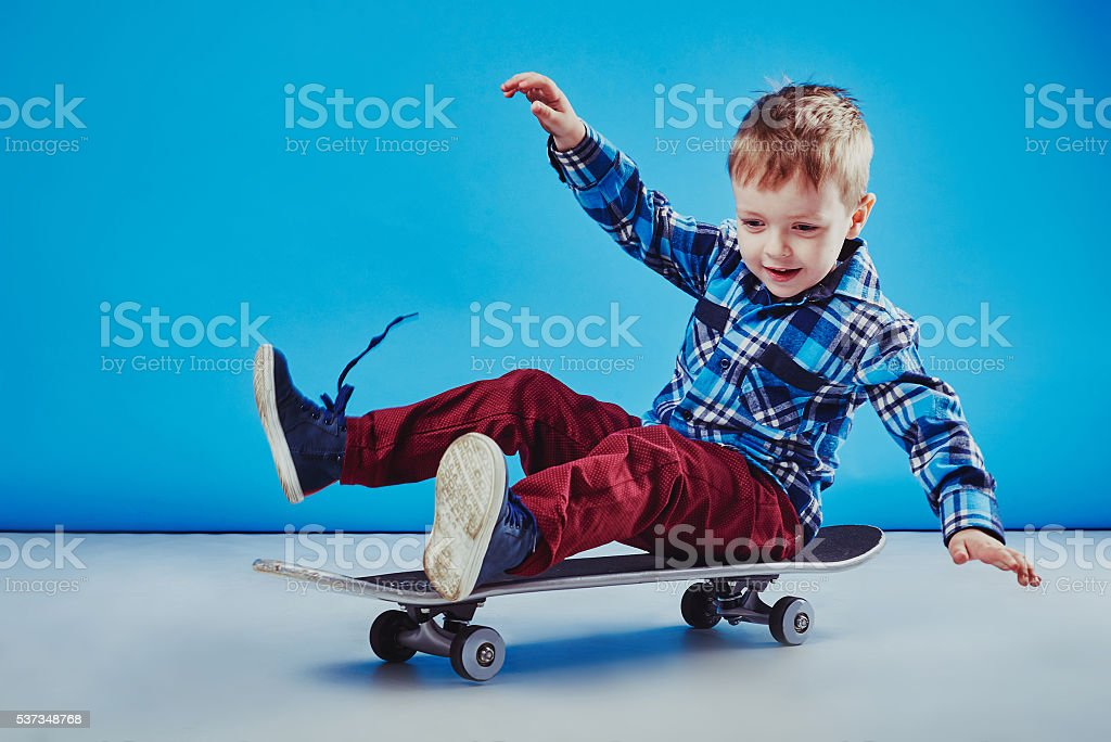 Happy boy riding skateboard stock photo