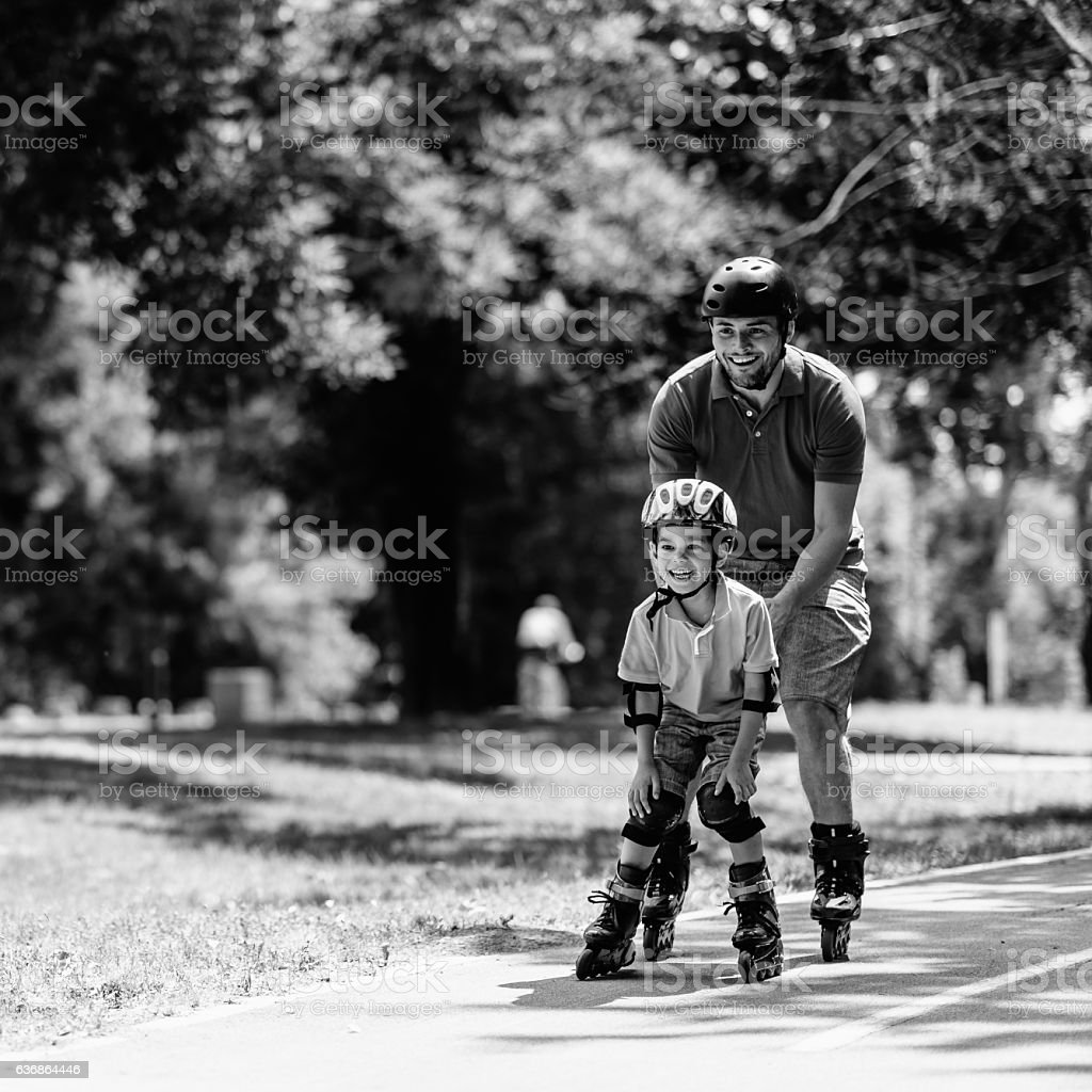 Happy boy roller skating with father stock photo