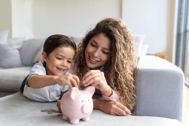Glücklicher Junge spart Geld in seinem Sparschwein – Foto