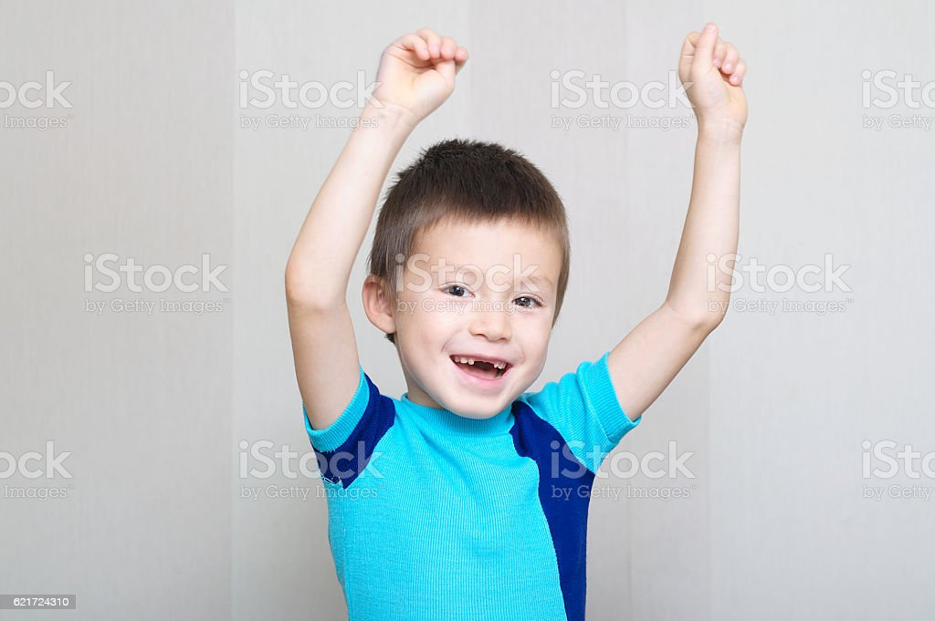 happy boy shouting with hands up stock photo
