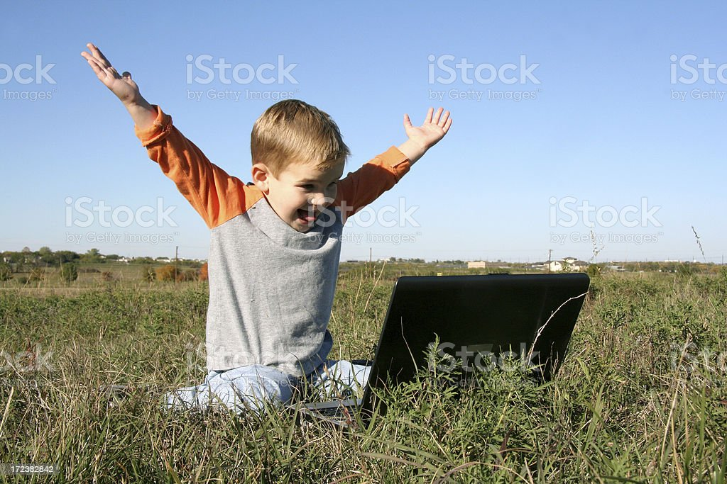 Happy Boy Sitting In A Field Using Computer royalty-free stock photo