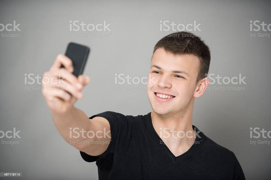 Happy Boy Taking Self Portrait With Smart Phone stock photo