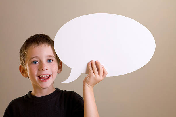 Happy boy talking with speech bubble stock photo