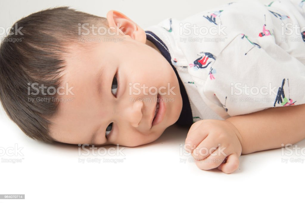 Happy boy toddler lay down on the floor with smile face on white - Royalty-free Baby - Human Age Stock Photo