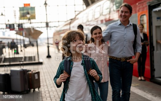 Happy boy traveling by train with his family – rail transportation concepts