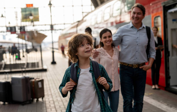 Happy boy traveling by train with his family Happy boy traveling by train with his family – rail transportation concepts railroad station platform stock pictures, royalty-free photos & images