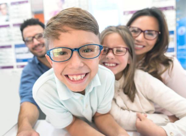 Fröhlicher junge versucht Gläser im optischen Shop mit seiner Familie – Foto