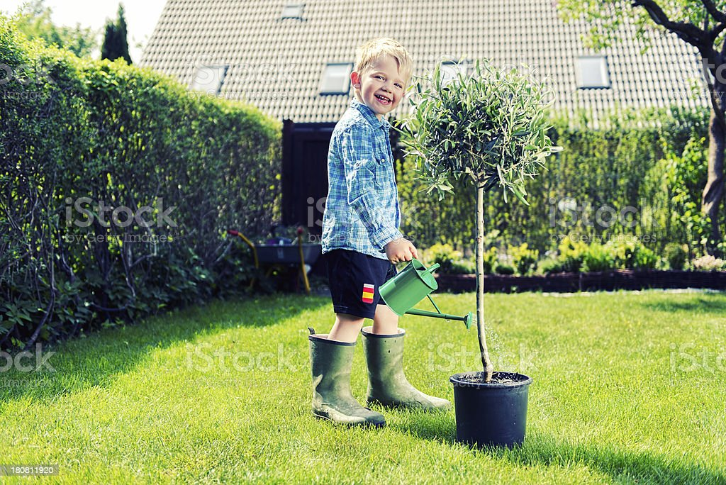 Happy boy uses watering can to make plant grow royalty-free stock photo
