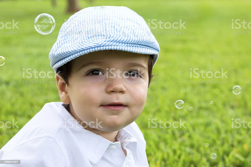 Happy boy wearing a flap cap with bubbles royalty-free stock photo