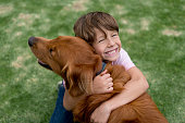 Portrait of a happy boy outdoors hugging a beautiful dog - lifestyle concepts