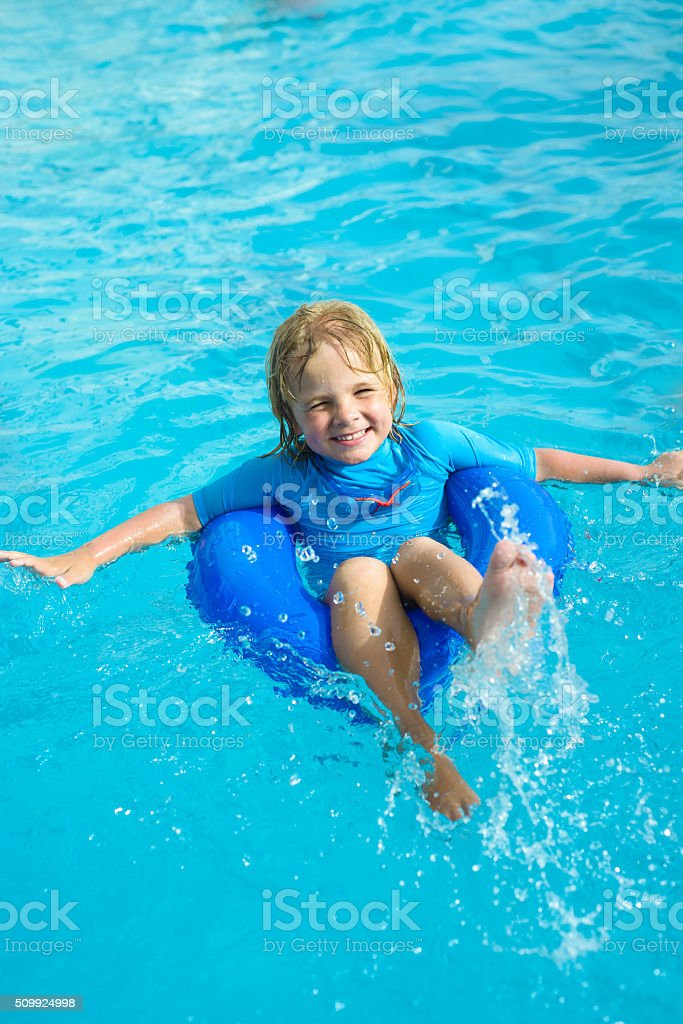 Happy boy with blue life ring has fun stock photo
