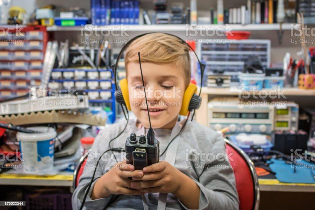Fröhlicher Junge mit Kopfhörern mit Walkie-Talkie. – Foto