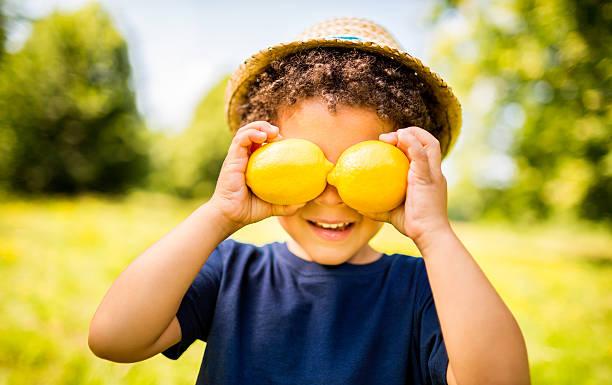 glückliche junge mit zitronen lächeln, während vitamin c konzept - zitronenspeise stock-fotos und bilder