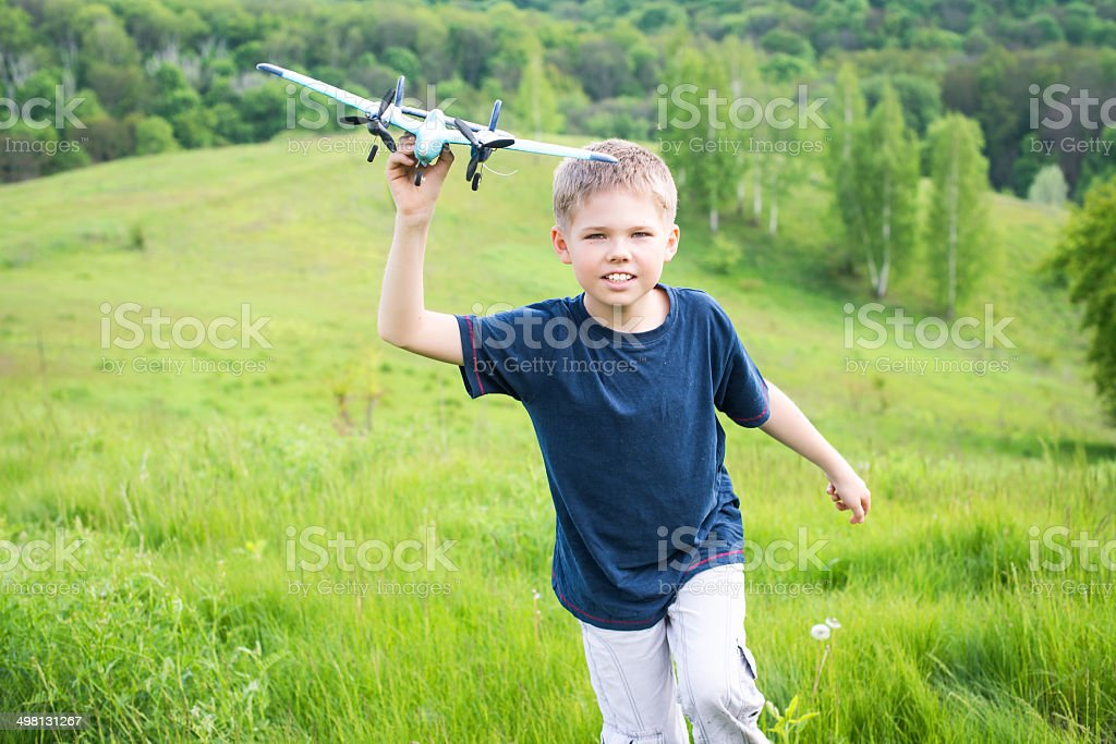 Happy boy with plane on a meadow in sunny day. stock photo
