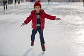 Happy boy with red hat and jacket, skating during the day, having fun