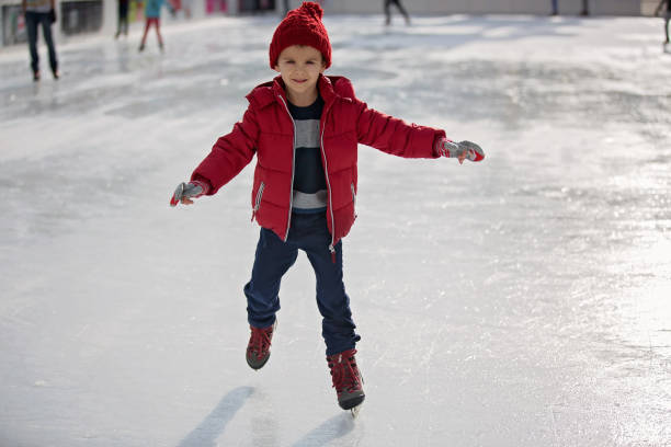 Happy boy with red hat, skating during the day, having fun Happy boy with red hat and jacket, skating during the day, having fun ice skating stock pictures, royalty-free photos & images